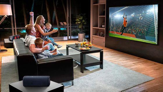 Una familia sentada en un sofá viendo fútbol en la televisión