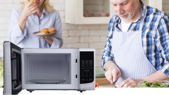 Un hombre mayor cocina en una cocina junto a un Microondas BGH abierto.