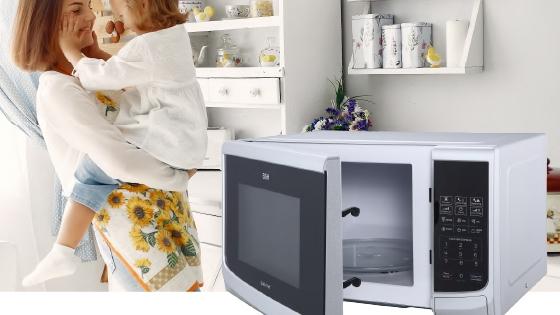 Madre e hija en una cocina junto con un Microondas BGH.